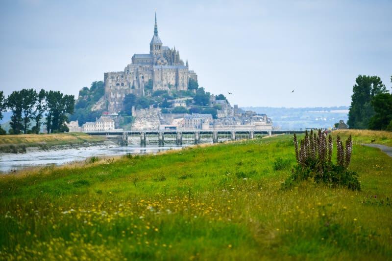 Il canale fa il suo modo fra i campi ed il terreno coltivabile fino a Mont Saint Michel, Saint Michel di FranceMont, Francia fotografia stock
