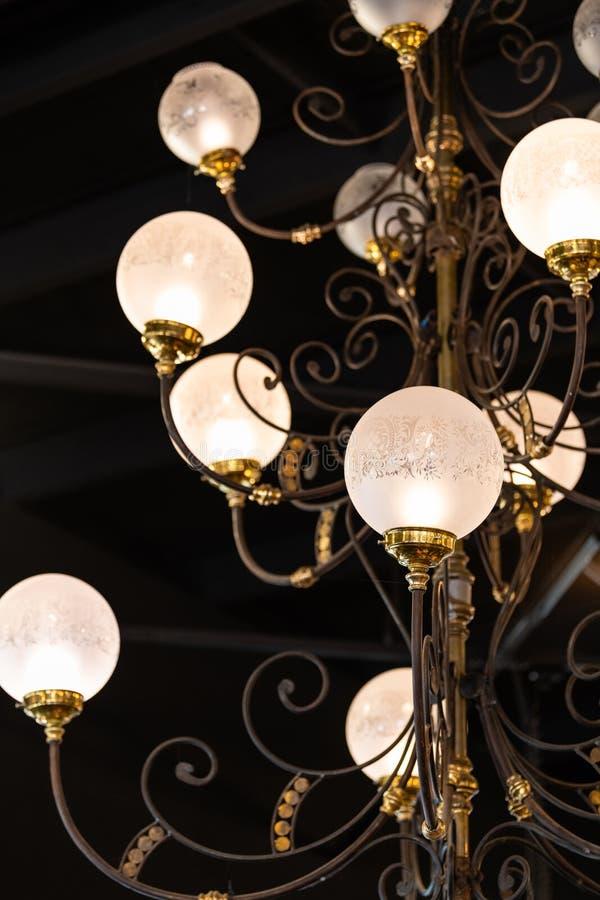 Il candeliere elaborato pende da un tetto con le decorazioni di art deco e le sfere di vetro rotonde immagini stock libere da diritti