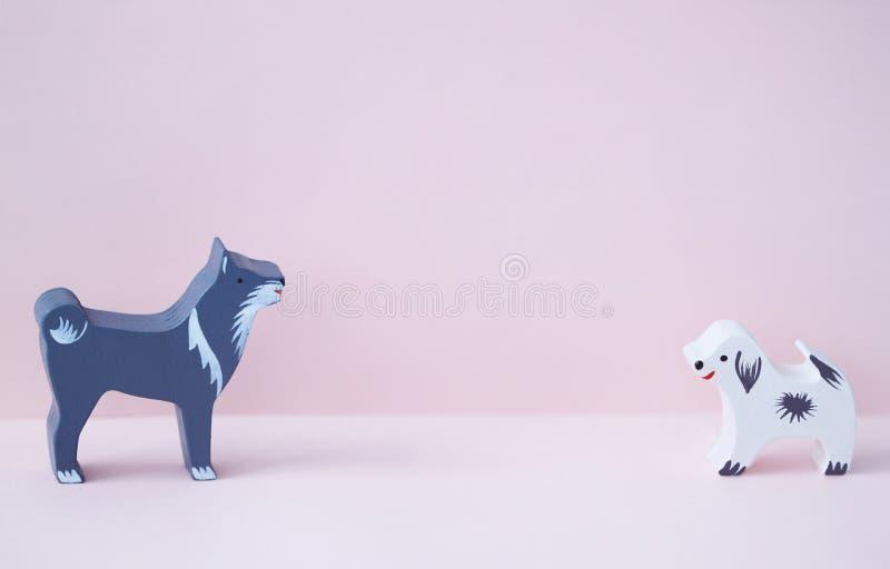Il cane grigio dei giocattoli minuscoli di legno ed il cucciolo bianco per i bambini su fondo rosa immagine stock libera da diritti