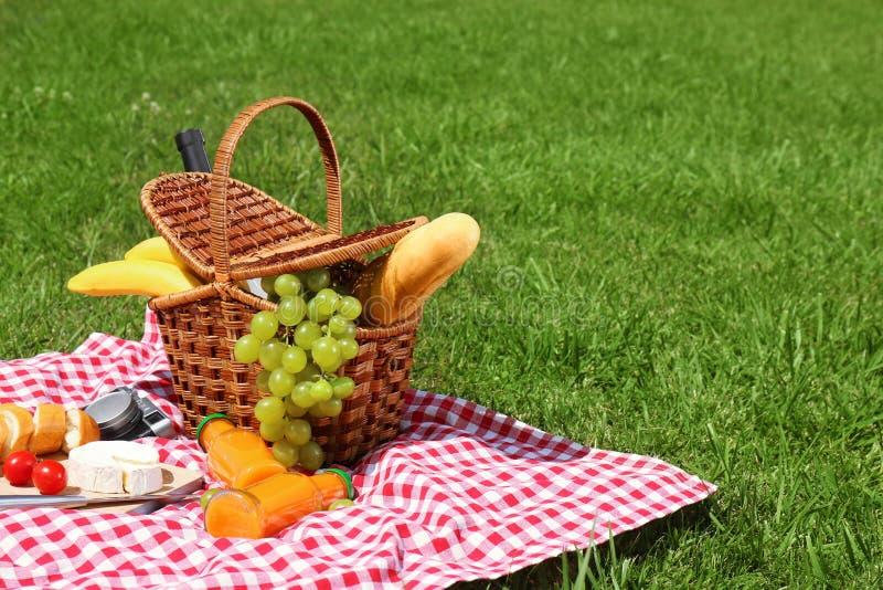 Il canestro con alimento sulla coperta ha preparato per il picnic fotografia stock