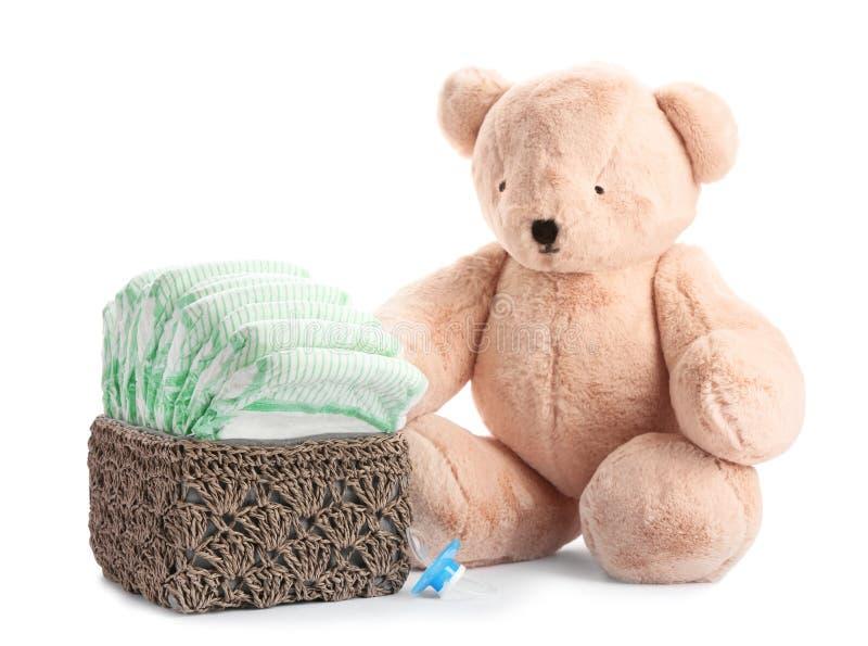 Il canestro con i pannolini, la tettarella e l'orsacchiotto riguardano bianco Accessori del bambino immagini stock