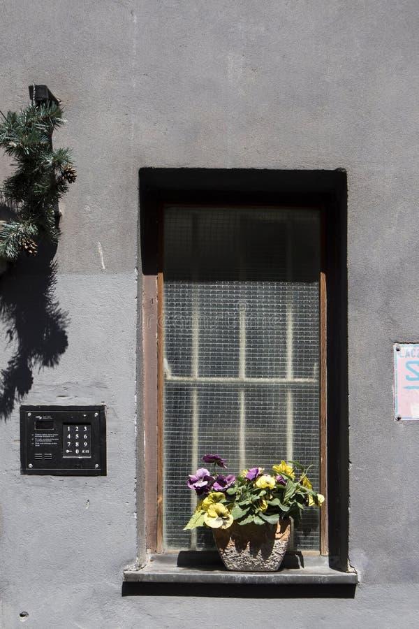 Il canestro con le viole ed il mazzo artificiale dei tulipani, crisantemi, mughetti e ranuncoli, decora l'entrata t fotografie stock