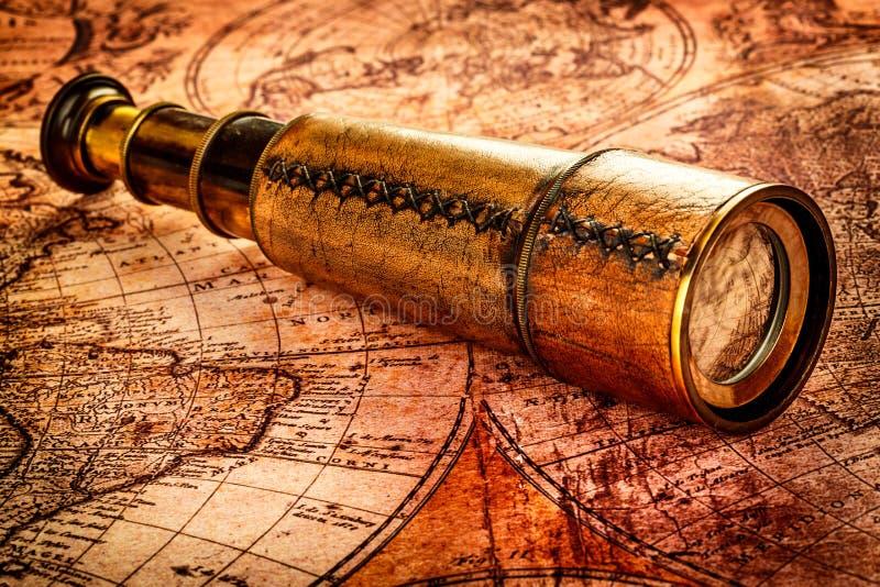 Il cannocchiale d'annata si trova su una mappa di mondo antica fotografia stock