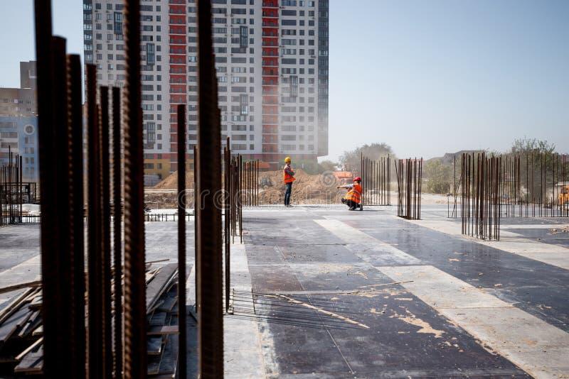 Il cantiere contro lo sfondo di una costruzione multistorey Due costruttori stanno funzionando immagini stock libere da diritti