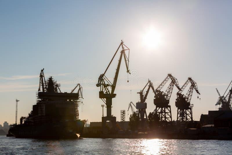 Il cantiere navale della siluetta ha macchina della gru, l'industria del cantiere navale immagine stock