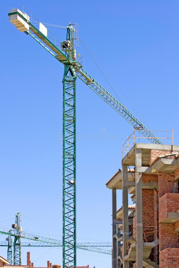 Il cantiere spagnolo tipico con la metà ha costruito la proprietà e la gru fotografie stock
