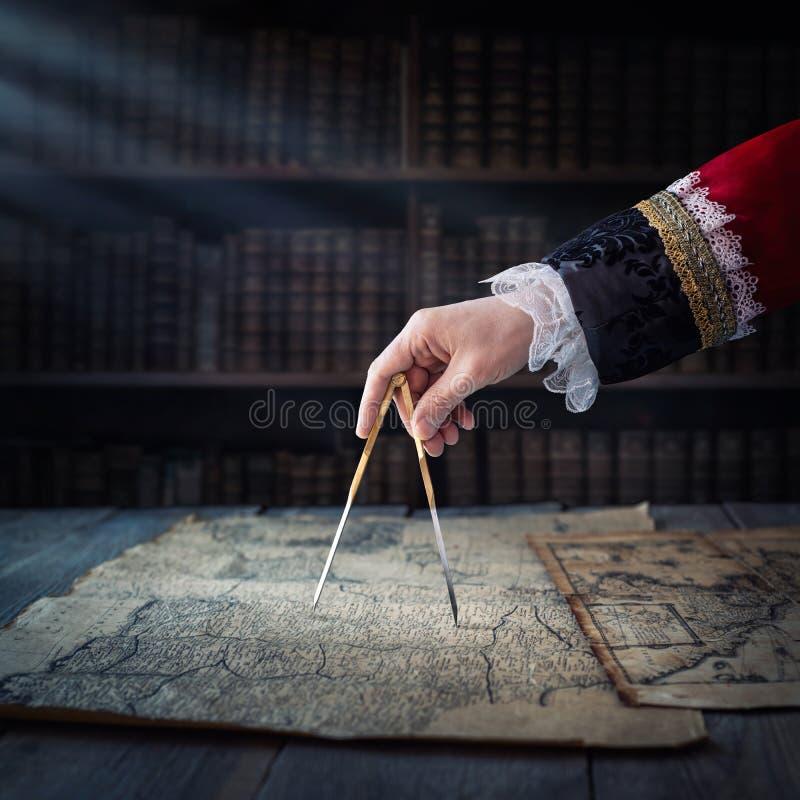 Il capitano di vecchia nave pavimenta il corso con l'aiuto delle mappe d'annata e del divisore nautico Vecchia scoperta, esplorat fotografia stock