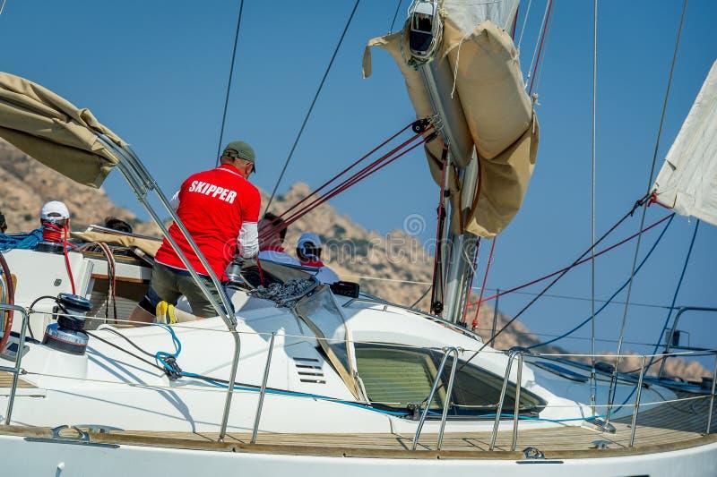 Il capitano sta lavorando alla sua barca a vela durante la corsa fotografie stock