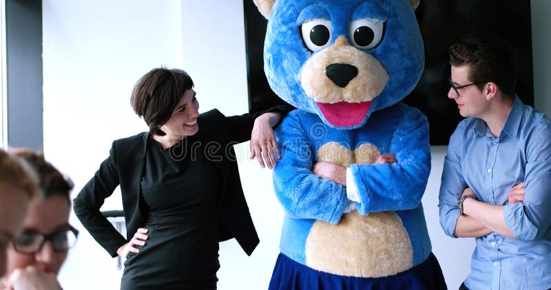 Il capo dresed come orso divertendosi con la gente di affari in d'avanguardia di fotografie stock