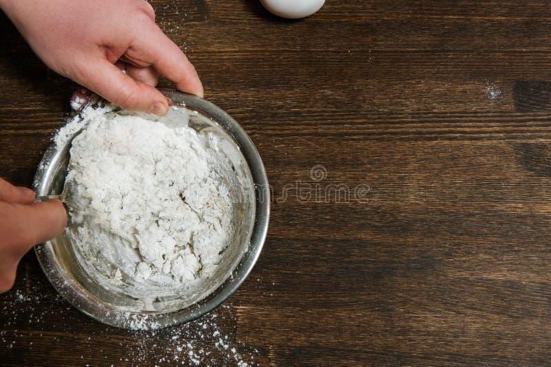 Il capo mescola la pasta in ciotola sulla tavola fotografia stock