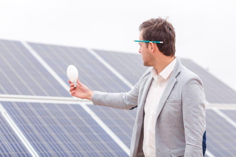 Il capo tiene una lampadina nella suoi mano e sguardo contro lo sfondo dei pannelli solari fotografia stock libera da diritti
