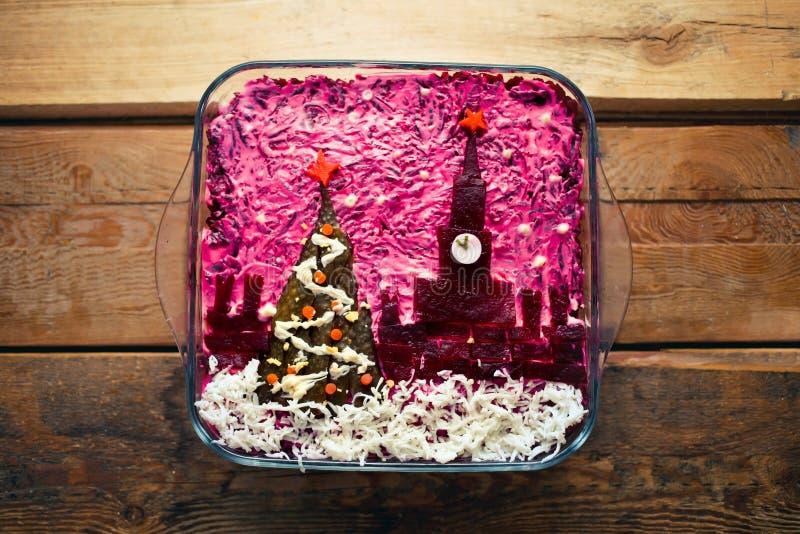 Il Capodanno domestico è insalata di aringhe sotto un cappotto con la decorazione del Cremlino russo e un albero su uno sfondo di fotografia stock libera da diritti