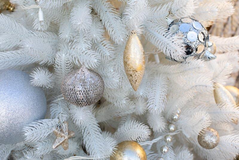 Il Capodanno dorato decora giocattoli su un albero di Natale di plastica bianco Palla a stella di Icicle appesa a rami di abete e fotografia stock libera da diritti
