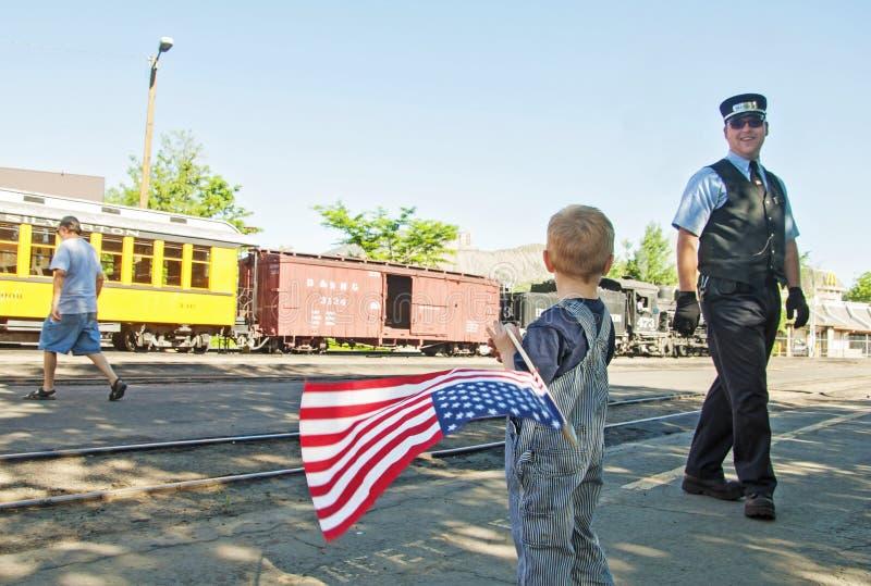 Il capotreno sorride alla bandiera americana d'ondeggiamento del ragazzo immagini stock
