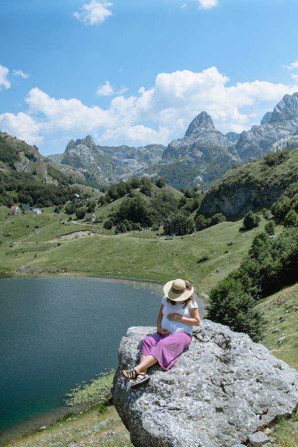 Il cappello d'uso della donna incinta si siede su una grande roccia nel backgroun fotografia stock libera da diritti