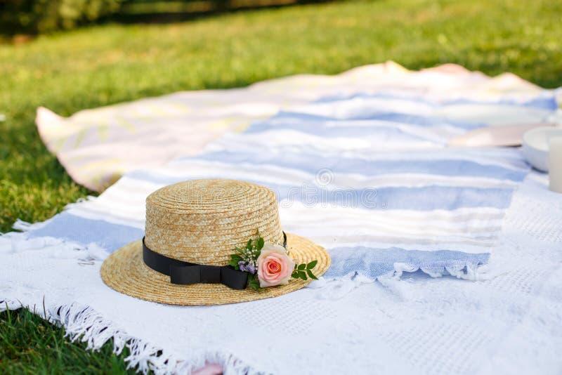 Il cappello di paglia con i fiori freschi mette su una coperta bianca di picnic al fondo luminoso del giorno di estate del prato  immagini stock