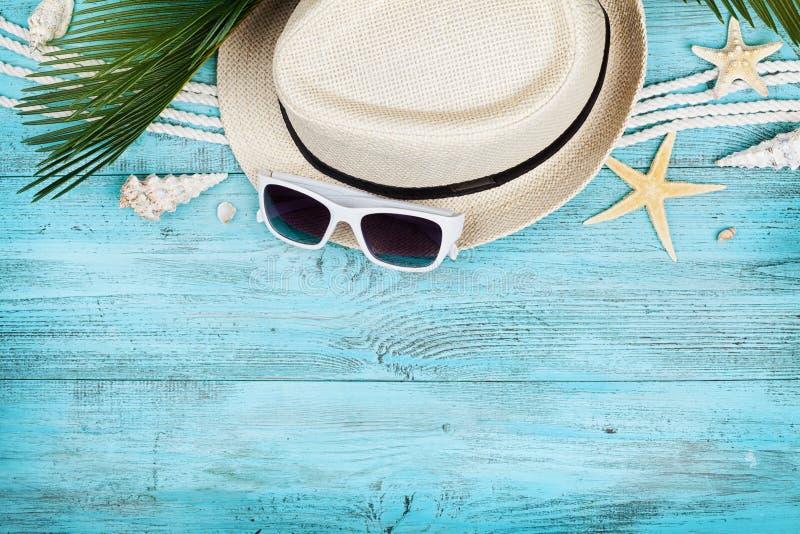 Il cappello di paglia, gli occhiali da sole, le foglie di palma, la corda, la conchiglia e le stelle marine sulla vista di legno  fotografia stock