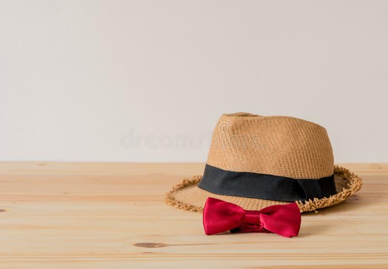 Il cappello e la cravatta a farfalla rossa sono disposti sul pavimento di legno immagine stock libera da diritti