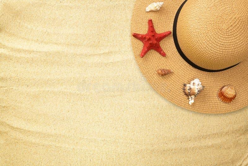 Il cappello e le conchiglie di paglia dell'estate, stelle marine rosse mettono su pianamente il fondo sabbioso di struttura Vista fotografia stock