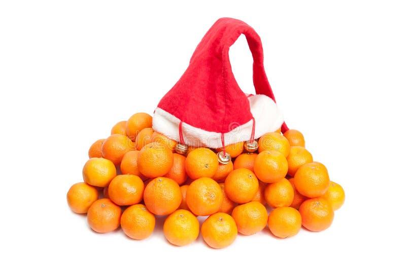 Il cappello rosso di Santa che si trova sul mucchio dei mandarini fertili fotografia stock libera da diritti