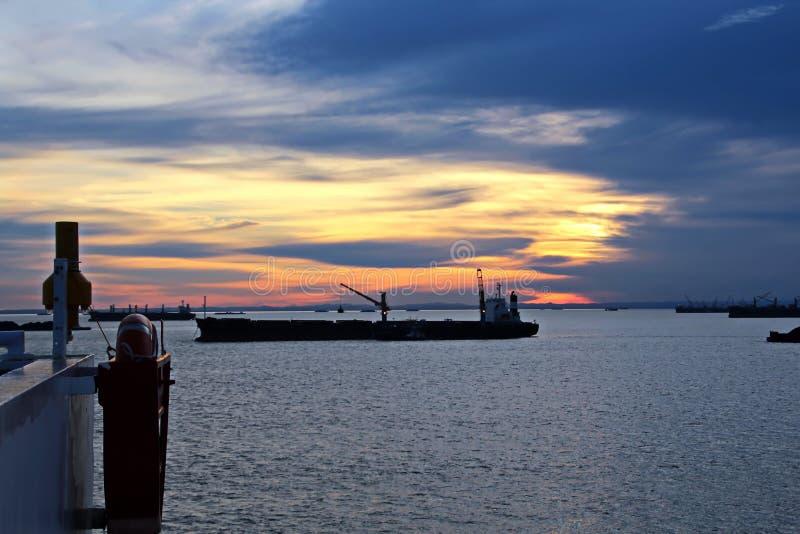 Il carbone di caricamento da carico barges su un porta rinfuse che usando le gru e le gru a benna della nave al porto di Samarind fotografie stock
