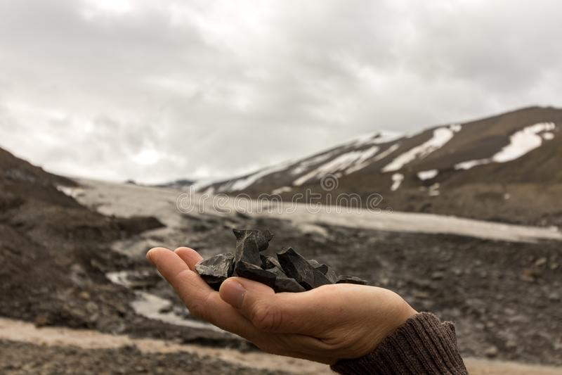 Il carbone femminile della tenuta della mano ha trovato dal ghiacciaio di Longyear, che è visto nei precedenti Paesaggio artico d fotografia stock libera da diritti
