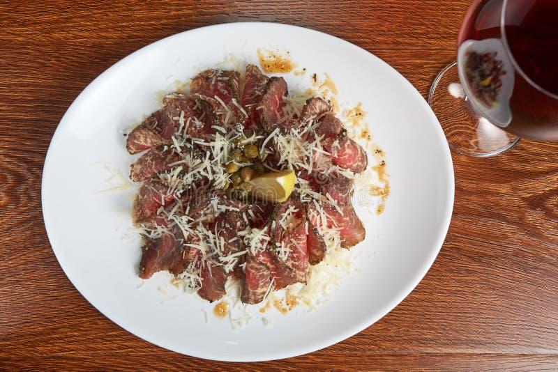 Il carpaccio, carne affumicata con formaggio grattugiato, limone, capperi, con salsa, vicino è un vetro di vino rosso, primo pian fotografia stock libera da diritti