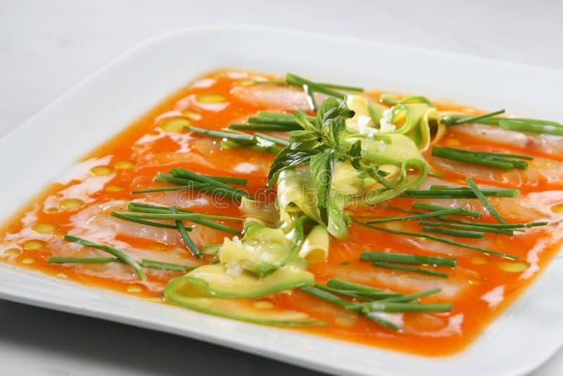 Il carpaccio di color salmone, fette sottili di salmone ha condito con olio d'oliva e l'avocado immagine stock