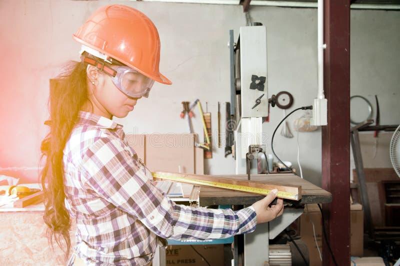 Il carpentiere abbastanza asiatico della donna sta misurando la lunghezza di legno con nastro adesivo per il taglio fotografia stock