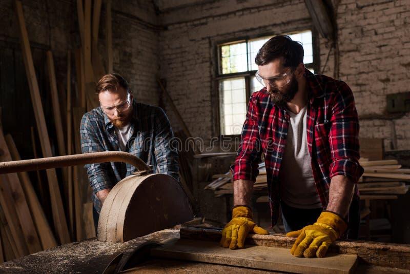 il carpentiere barbuto in protettivo googla e guanti facendo uso della condizione della sega e del partner della macchina immagine stock libera da diritti