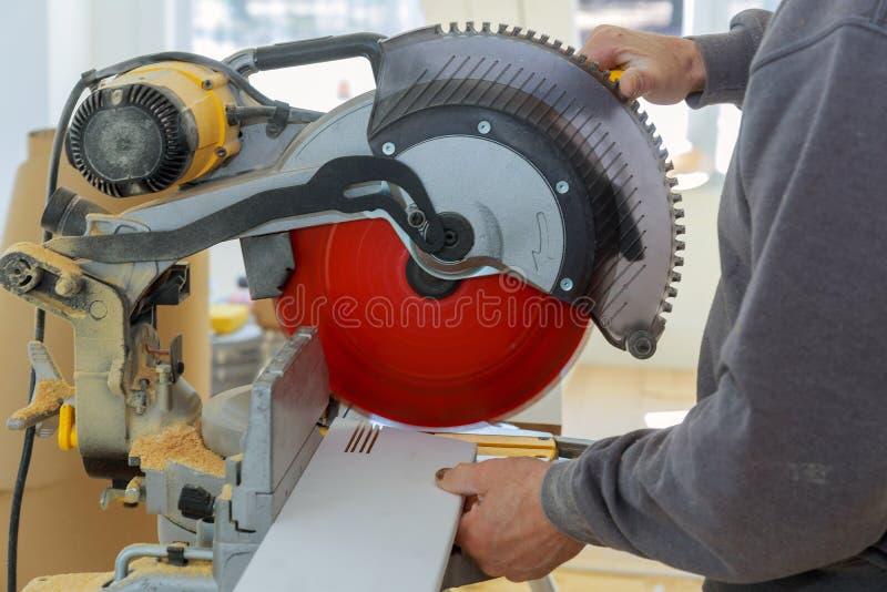Il carpentiere che lavora facendo uso della rotazione circolare della sega ha visto la battiscopa di legno di taglio fotografia stock libera da diritti