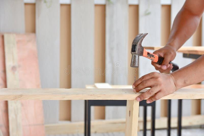 Il carpentiere che per mezzo del martello ha colpito un chiodo fotografie stock libere da diritti