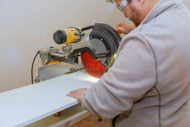 Il carpentiere dell'uomo che per mezzo dell'elettrotipia circolare ha visto il taglio degli scaffali bianchi laminati fotografia stock