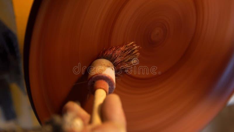 Il carpentiere dipinge il piatto di legno dalla spazzola fotografia stock