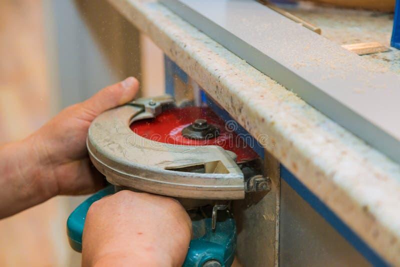 Il carpentiere facendo uso della circolare ha visto il taglio del foro tagliato in mobilia della cucina fotografie stock libere da diritti
