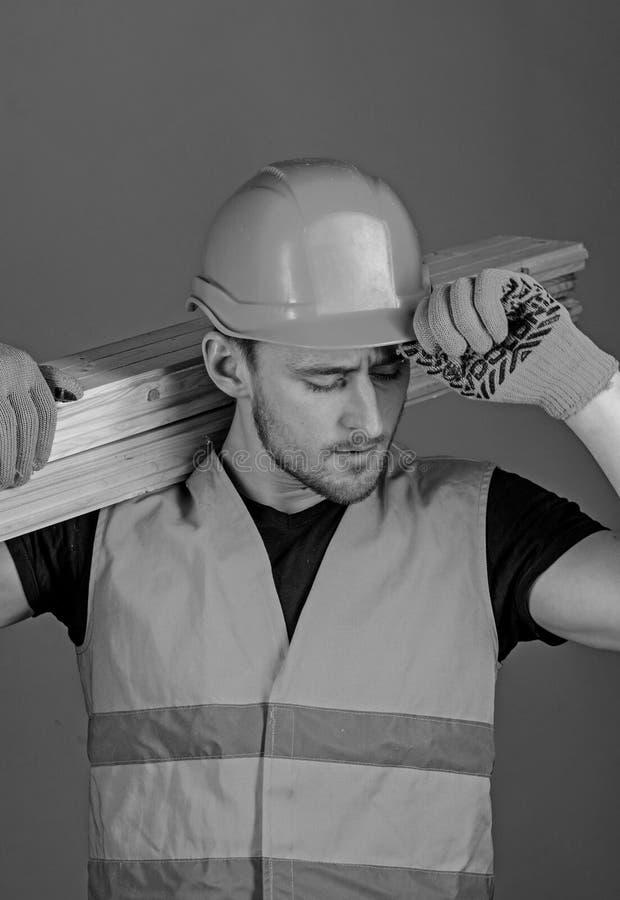 Il carpentiere, falegname, forte costruttore sul fronte occupato porta il fascio di legno sulla spalla Concetto di protezione e d fotografia stock
