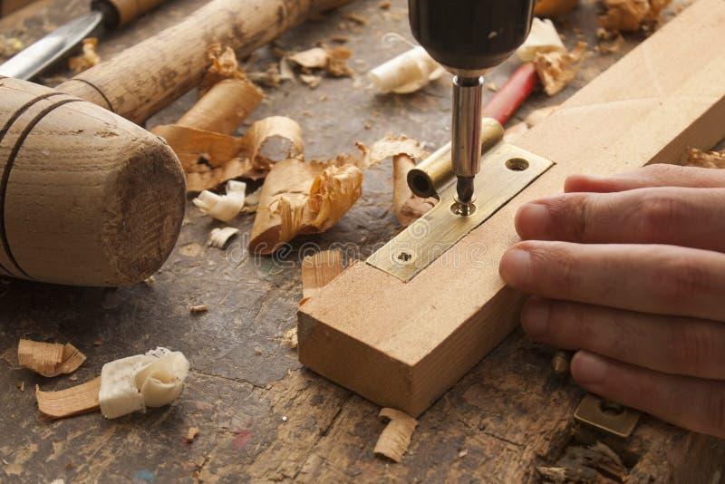 Il carpentiere ha avvitato una cerniera immagine stock