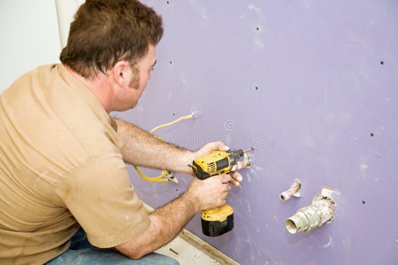 Il carpentiere installa il muro a secco fotografia stock libera da diritti