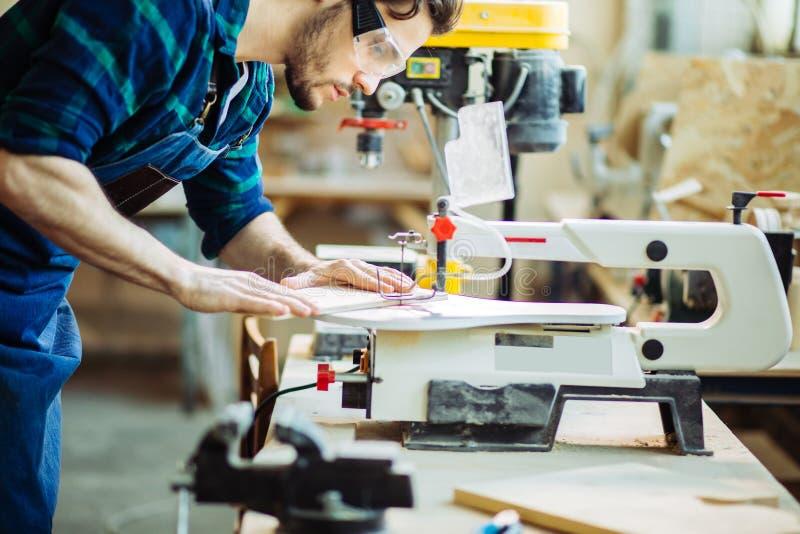 Il carpentiere si è impegnato nell'elaborazione del legno alla segheria fotografia stock libera da diritti