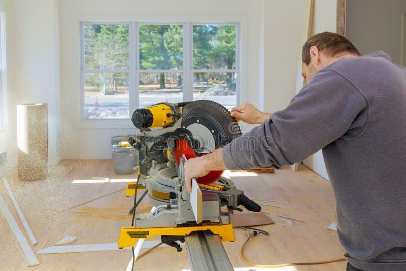 Il carpentiere sul lavoro facendo uso della circolare ha visto il taglio della battiscopa di legno dei modanature fotografia stock
