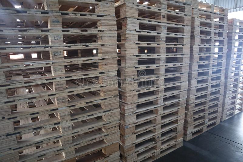 Il carrello elevatore ed i pallet di legno ammucchiano nel magazzino del carico per trasporto e la logistica fotografie stock libere da diritti