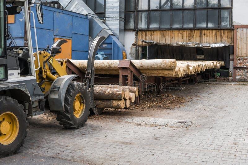 Il carrello elevatore a forcale afferra il legno in un impianto di lavorazione di legno Grande caricatore del ceppo che scarica u fotografie stock libere da diritti