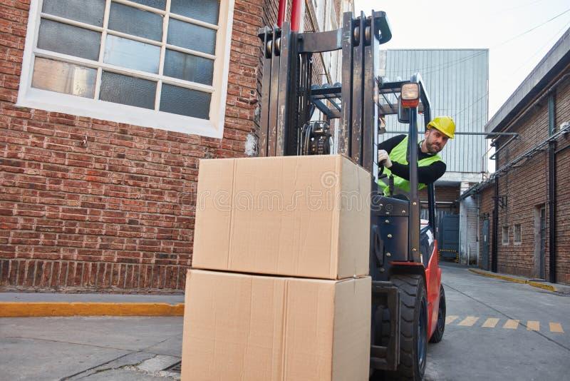 Il carrello elevatore trasporta i pacchetti del trasporto fotografie stock