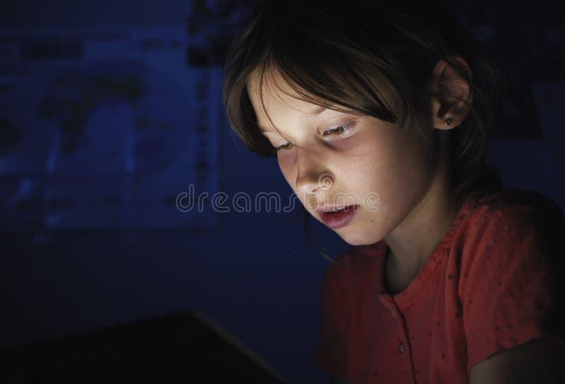 Il carrello ha sparato alla ragazza caucasica a letto che gioca la compressa in Internet alla luce blu scuro nell'ambito del blac immagine stock libera da diritti