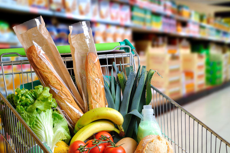Il carrello in pieno di alimento in navata laterale del supermercato ha elevato la vista fotografia stock