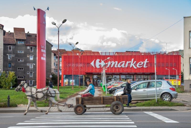 Il carretto del cavallo condotto dalla gente dalla comunità di Roma che passa davanti ad un Carrefour commercializza il supermerc fotografia stock