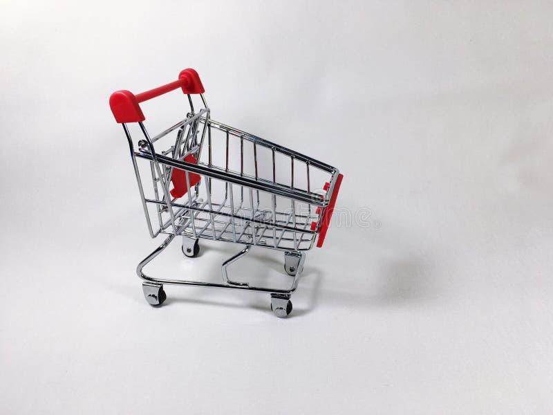 Il carretto del supermercato ha messo un contesto bianco fotografia stock