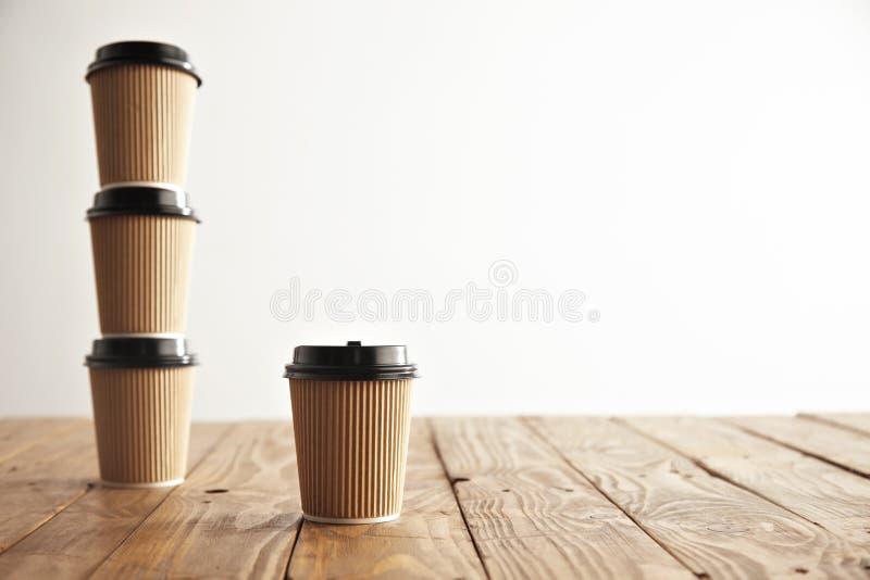 Il cartone di Brown porta via le tazze di carta con i berretti neri messi fotografia stock