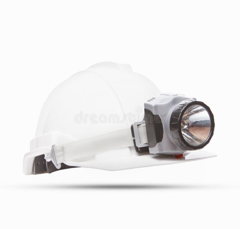 Il casco bianco di sicurezza nelle miniere con la lampada leggera ha isolato il fondo fotografia stock