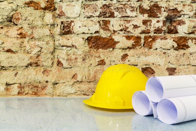 Il casco ed i disegni di sicurezza proiettano sul fondo del muro di mattoni immagini stock libere da diritti
